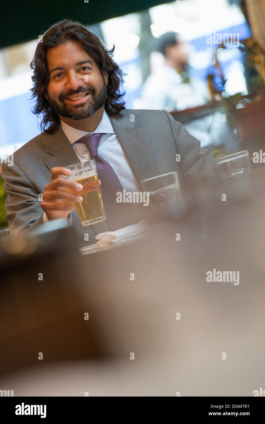 Business people. A Latino man seated at a table in a bar or cafe. - Stock Image