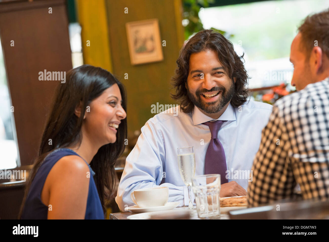 Business people. Three people seated around a table in a bar or cafe, having drinks. - Stock Image
