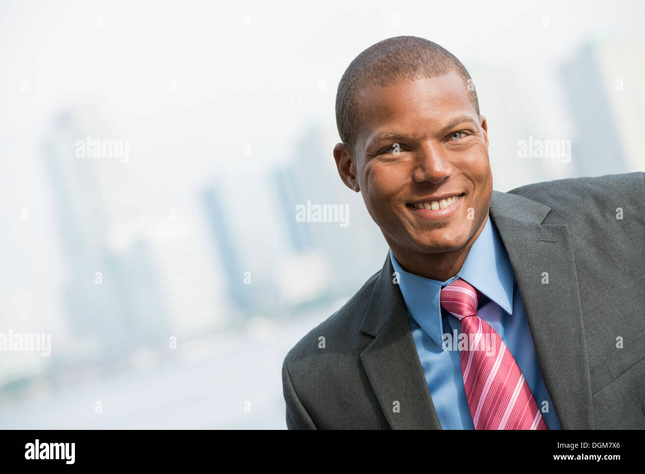 A young man in a business suit with a blue shirt and red tie. On a city street. Smiling at the camera. - Stock Image