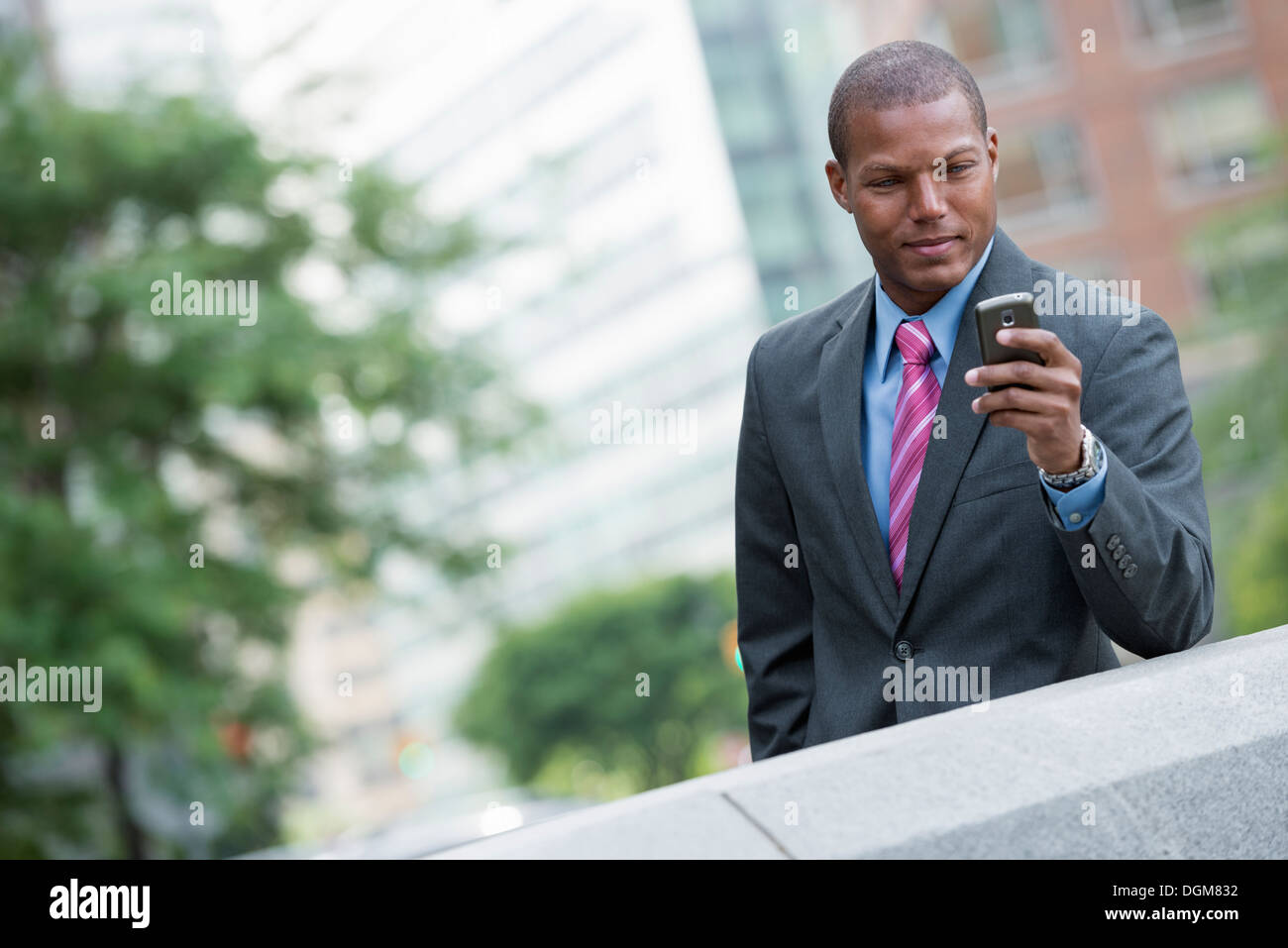 A young man in a business suit with a blue shirt and red tie. On a New York city street. Using a smart phone. - Stock Image
