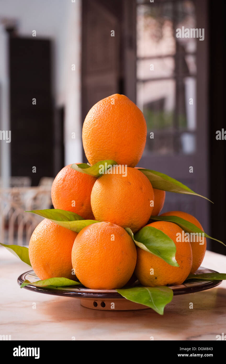 Pile of Moroccan oranges on ceramic dish - Stock Image