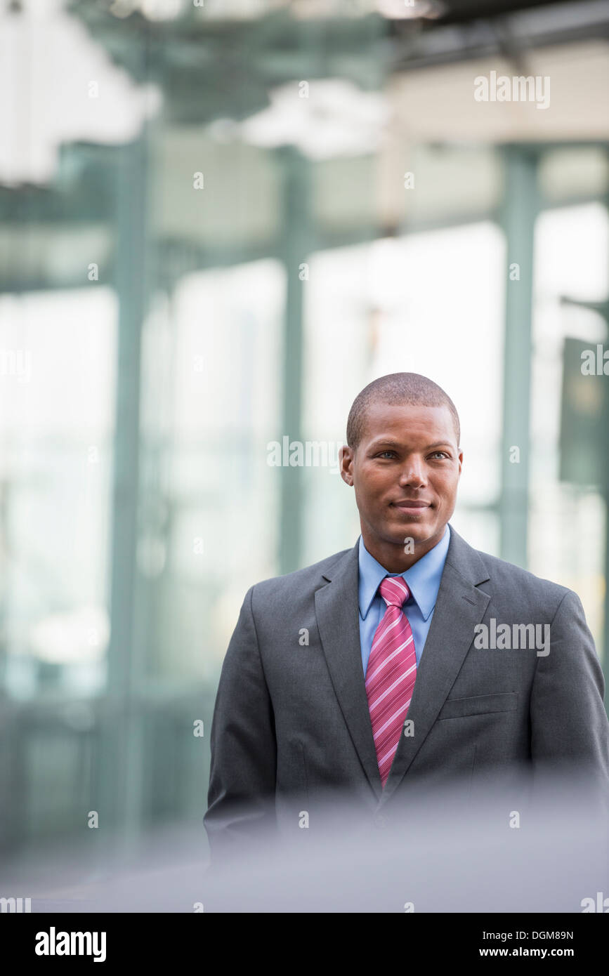 A young man in a business suit with a blue shirt and red tie. On a city street. - Stock Image