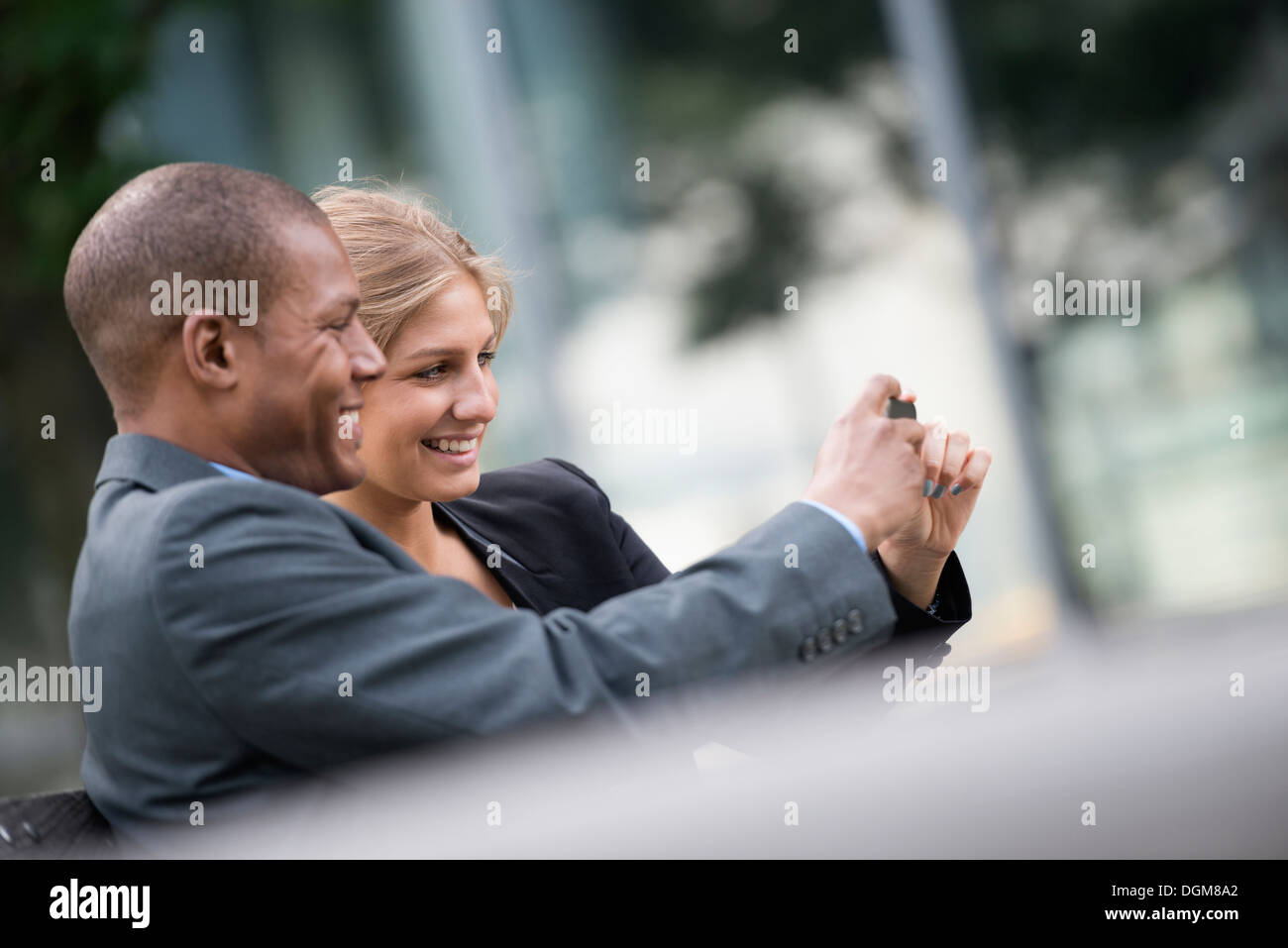 A young blonde woman man on New York city street Wearing business clothes Standing side by side taking selfy photograph smart - Stock Image