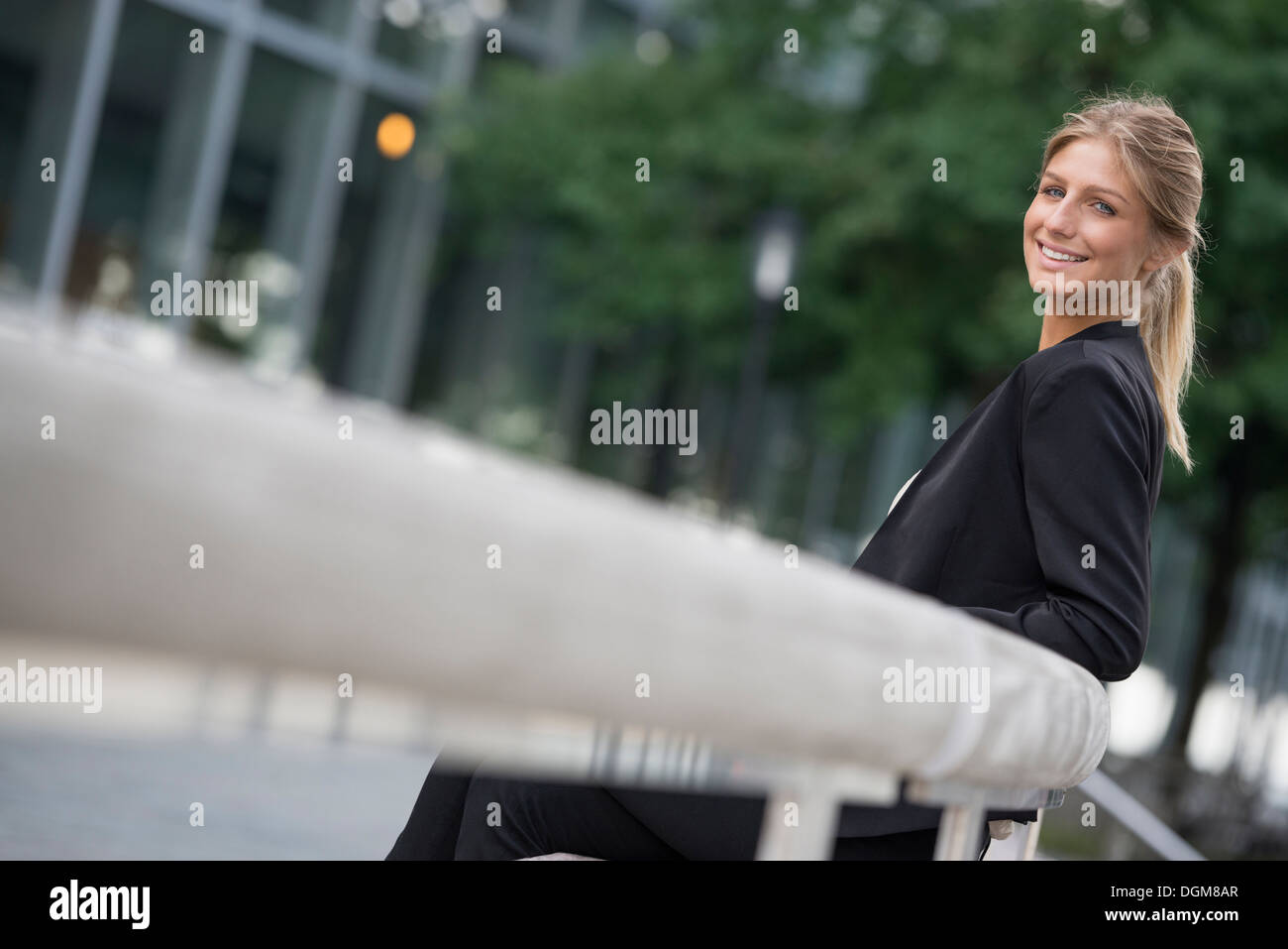 A young blonde woman on a New York city street. Wearing a black jacket. Stock Photo