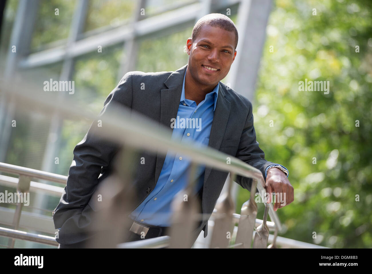 A young man in a jacket and open collared blue shirt, leaning on a railing in a city park in summer. Looking at Stock Photo
