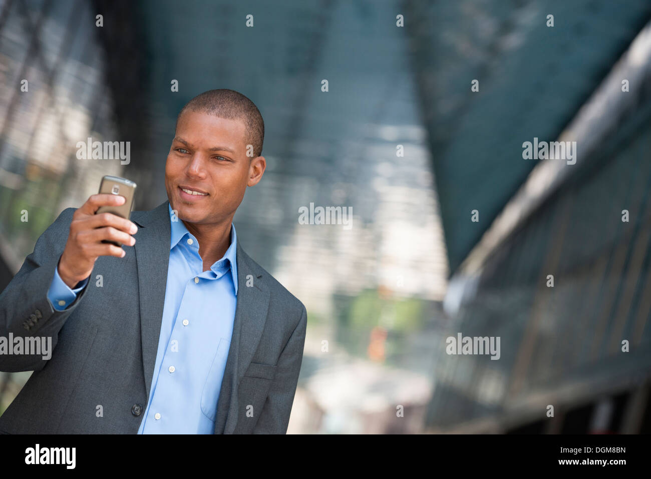 A businessman in a suit, with his shirt collar unbuttoned. On a New York city street. Using a smart phone. - Stock Image