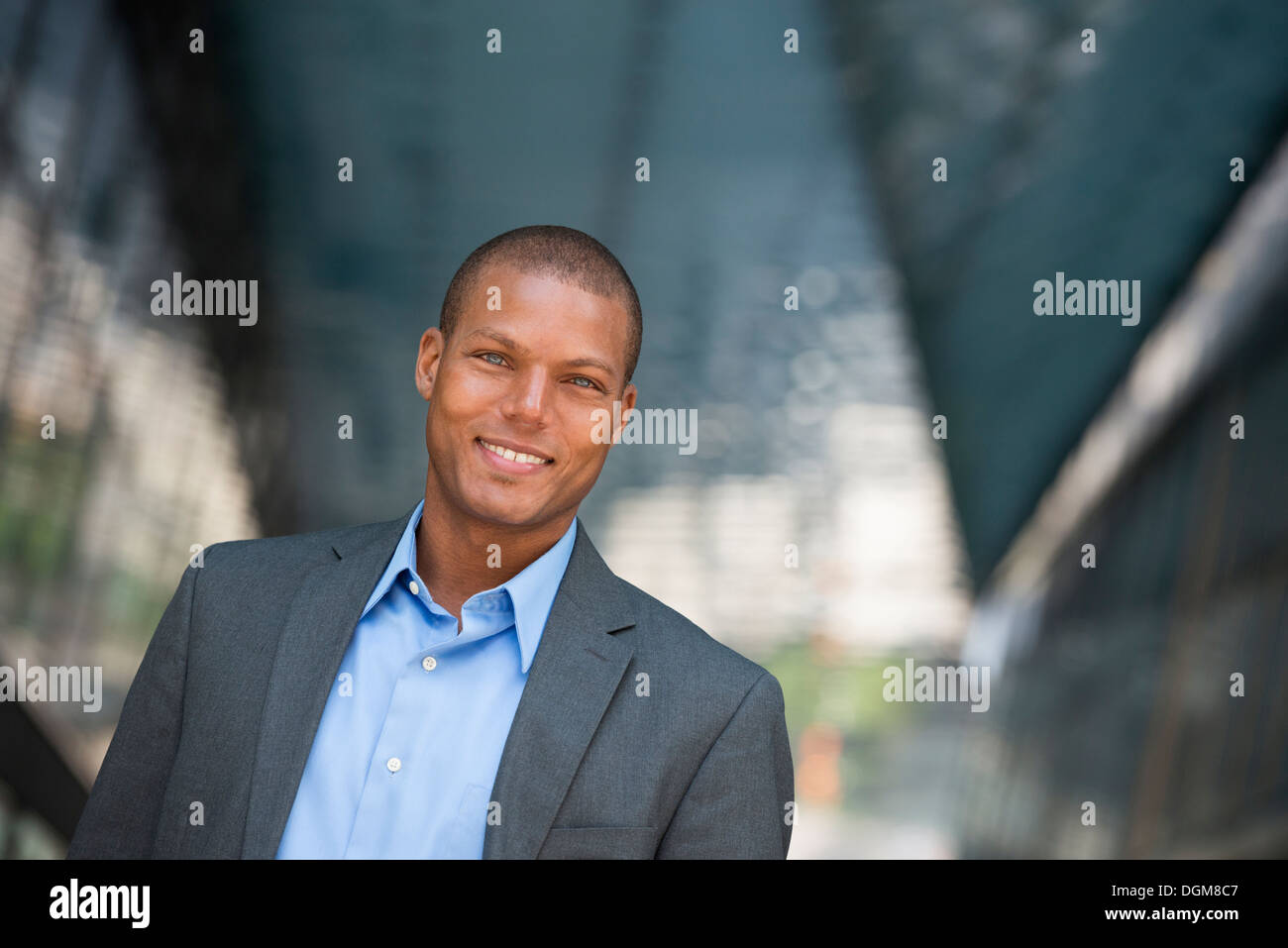 A businessman in a suit, with his shirt collar unbuttoned. On a New York city street. - Stock Image