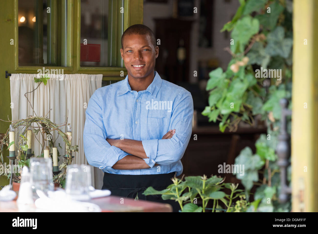 A man standing by the open window of a cafe or bistro, looking out with arms folded. - Stock Image
