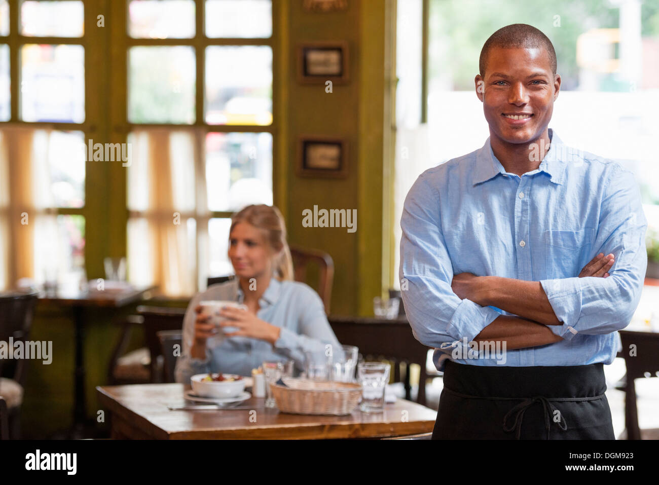 A couple in a city coffee shop. A woman sitting down checking a smart phone. A man standing up with arms folded. - Stock Image