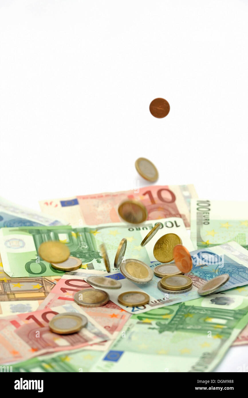 Euro coins falling on euro banknotes, raining money - Stock Image