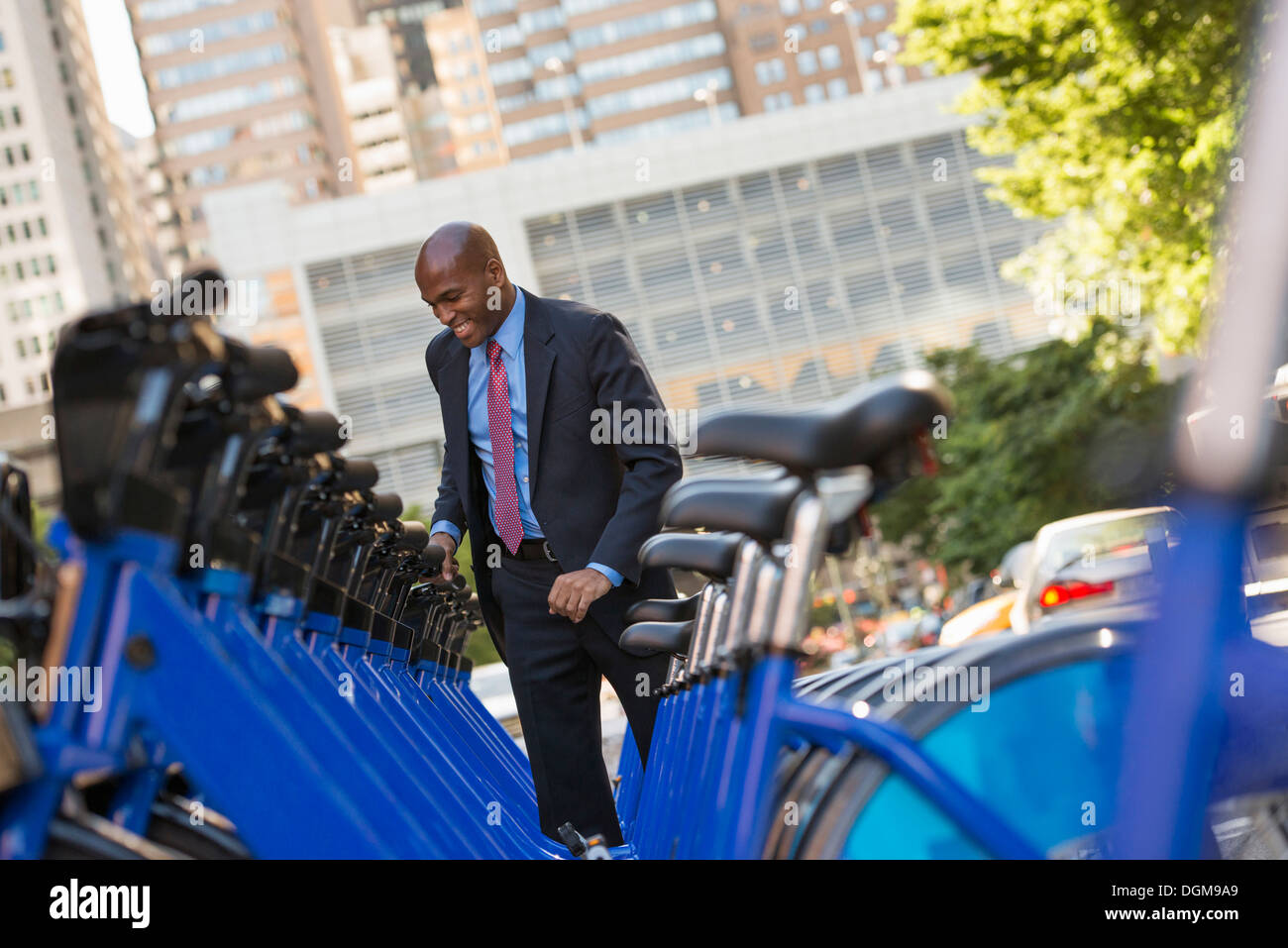 Business people. A man in a business suit beside a rack of rental bicycles. - Stock Image