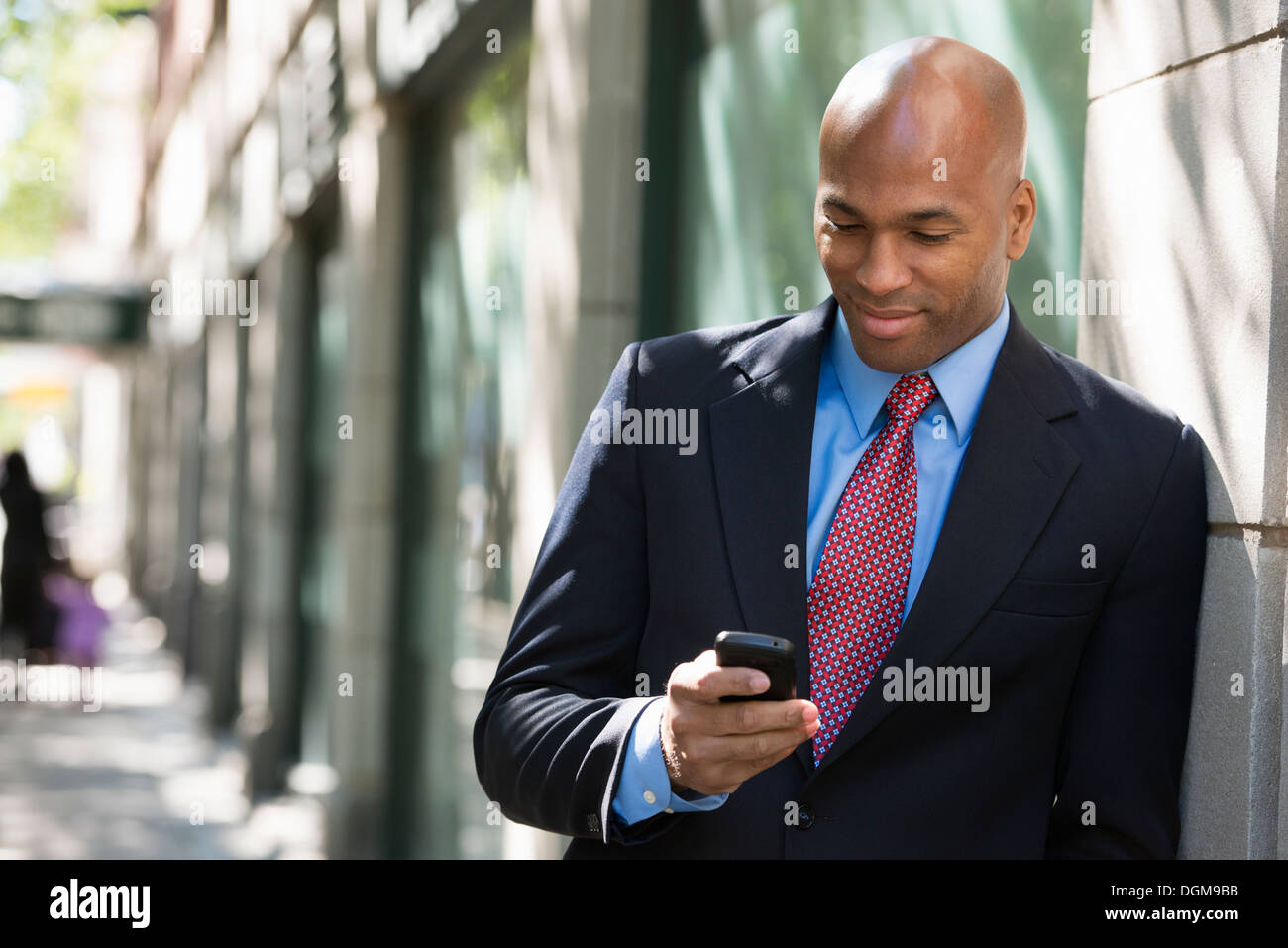 Business people. A businessman in a suit and red tie, checking his phone. - Stock Image
