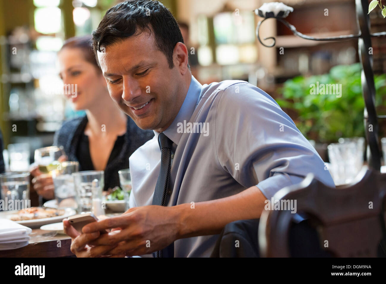 Business people. Three people around a cafe table, one of whom is checking their phone. - Stock Image