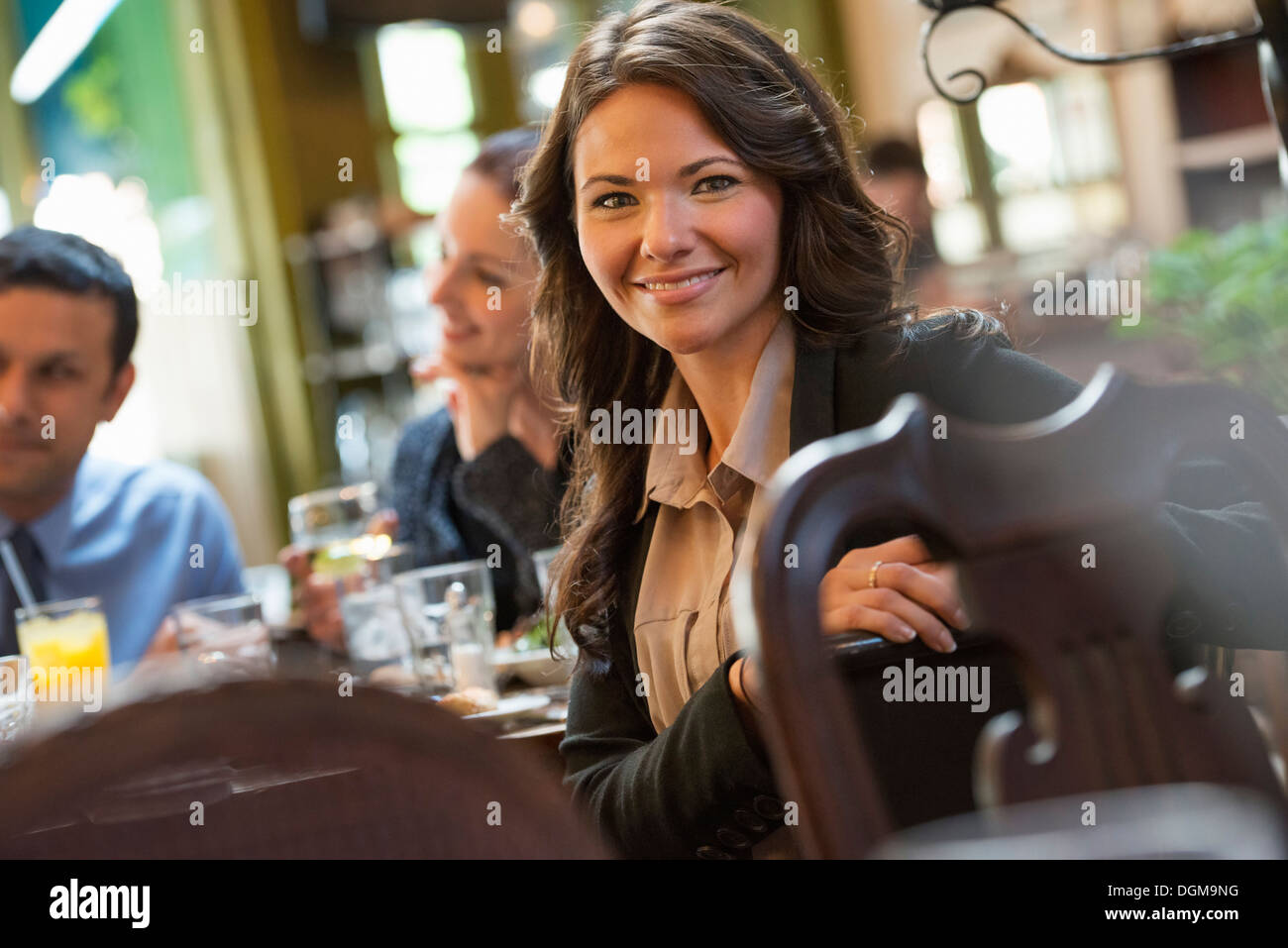 Business people. Three people around a cafe table, one woman turning to smile at the camera. - Stock Image