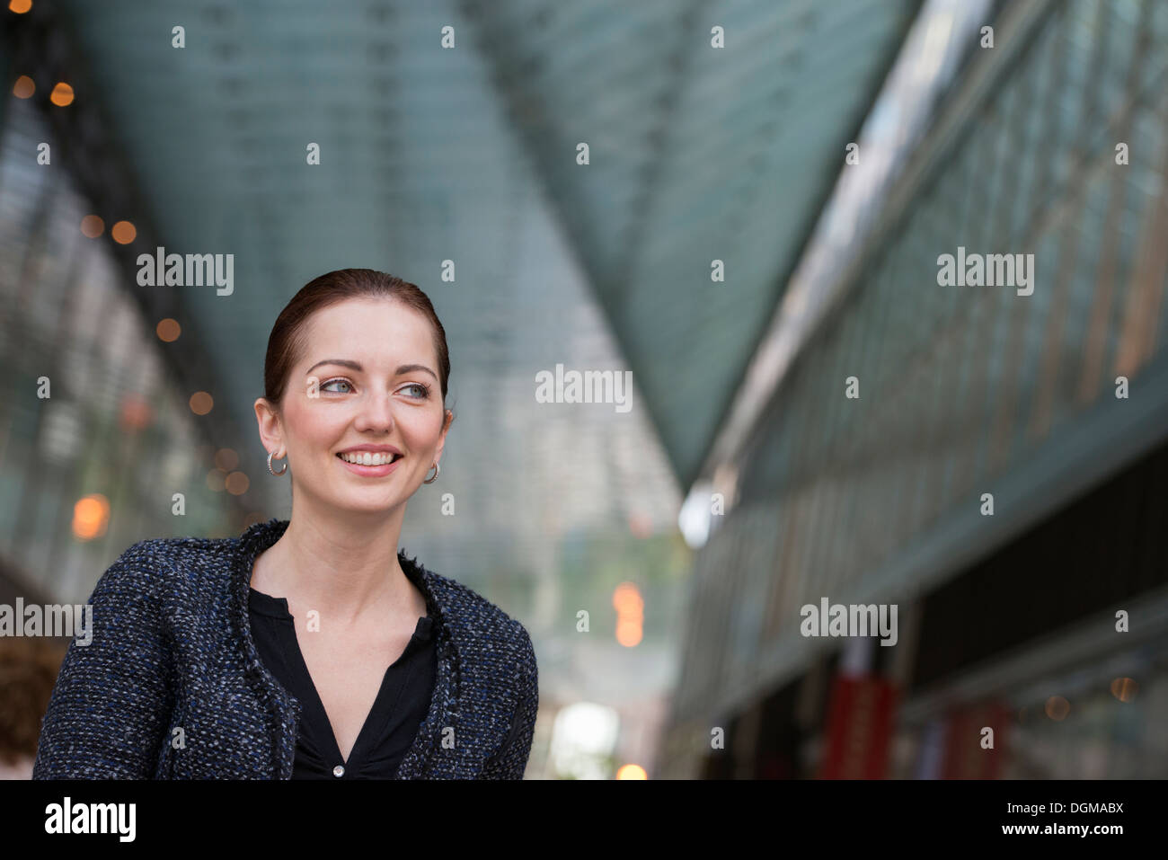 Business people outdoors. A woman in a grey jacket with her hair up, smiling. - Stock Image