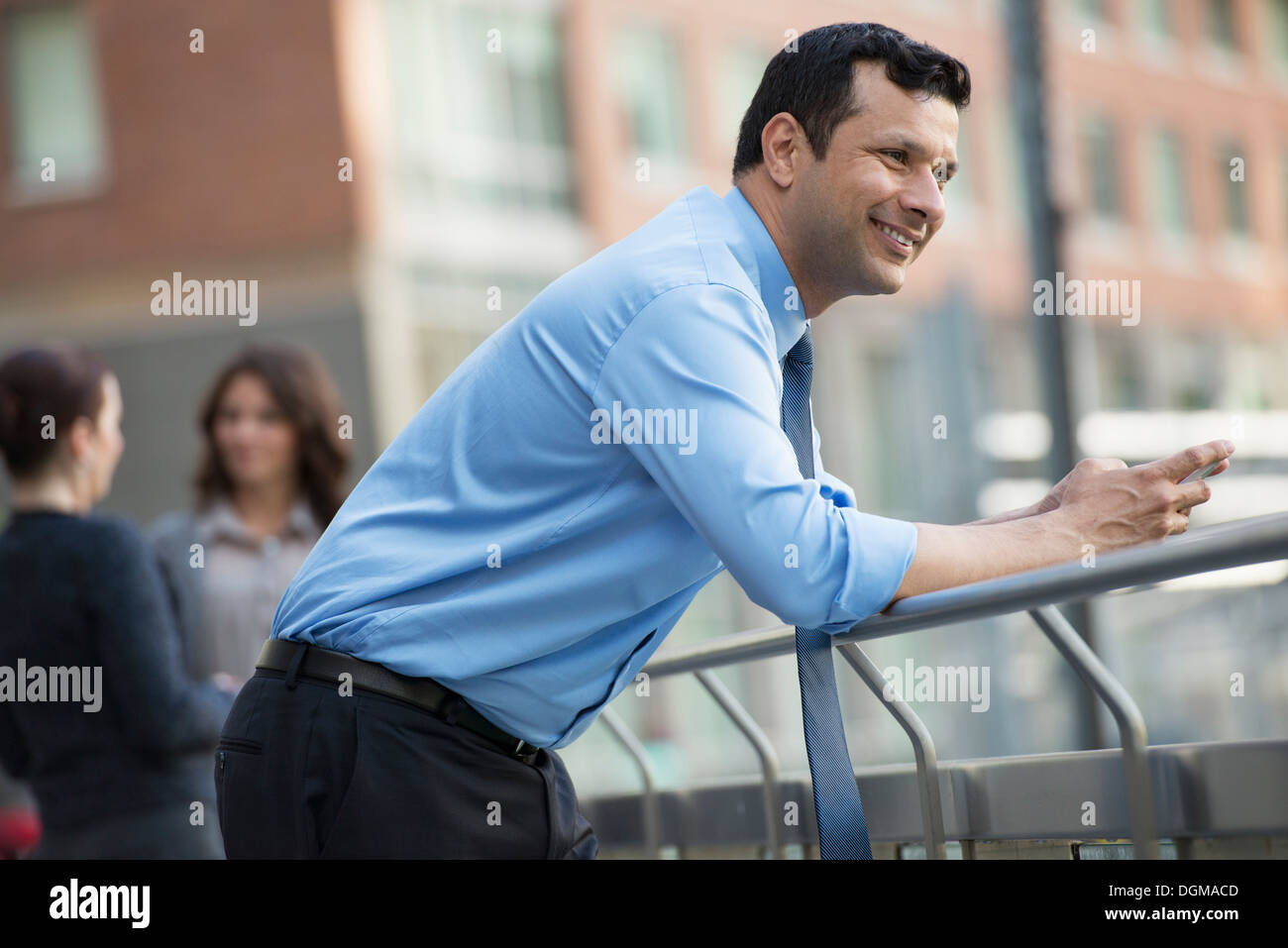 Business people outdoors. A latino businessman in shirt and tie, leaning on a railing. Relaxing. - Stock Image