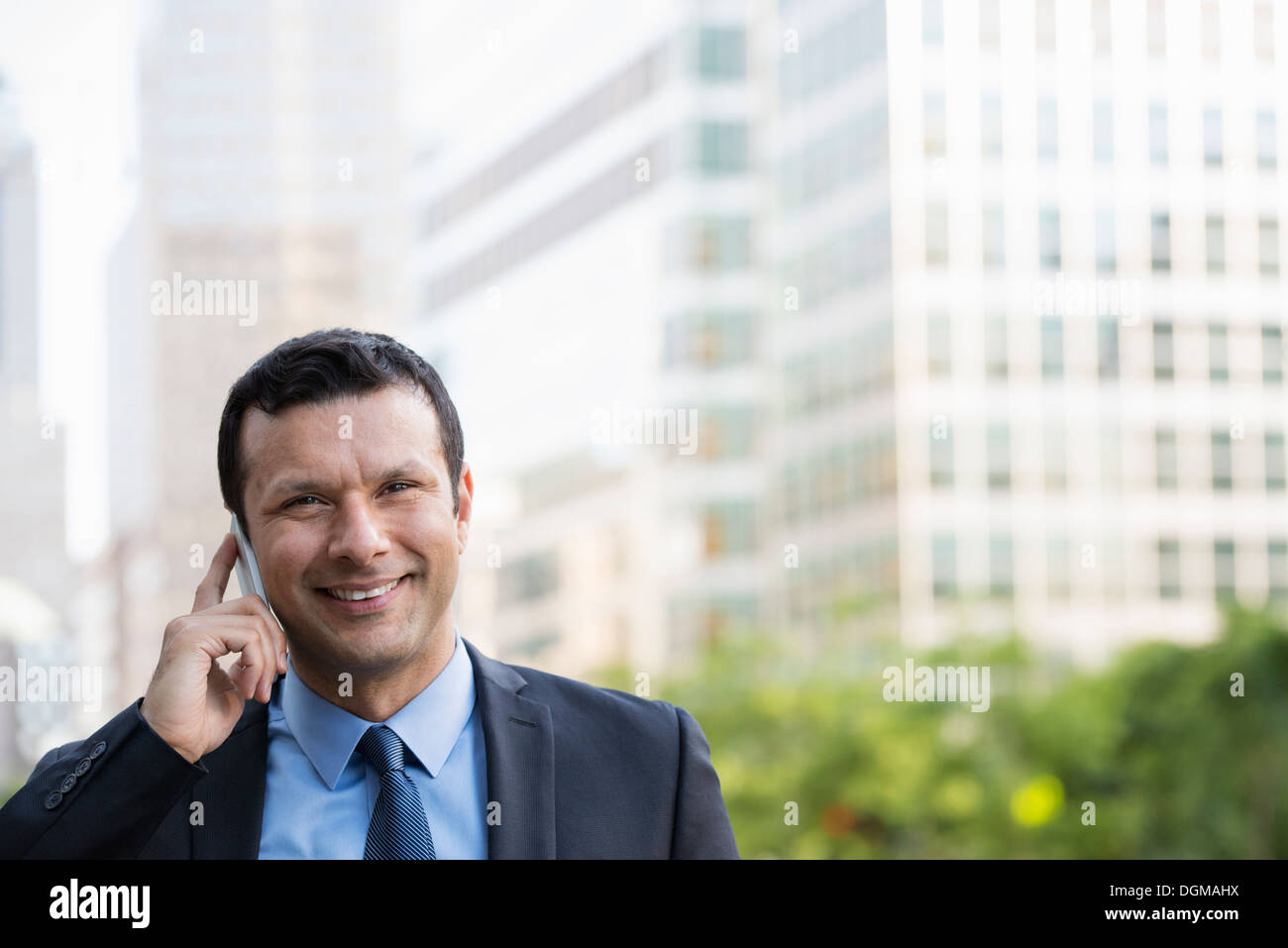 Business people. A latino businessman in business clothes. Using his phone. - Stock Image