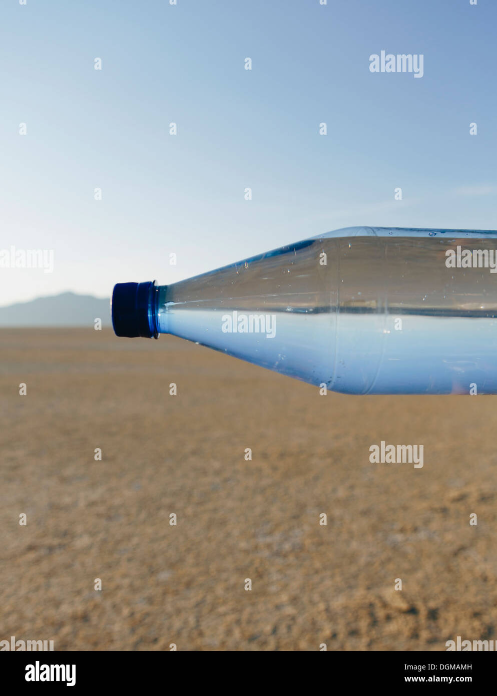 Black Rock Desert in Nevada. A bottle of water. Filtered mineral water. Sideways. The water level matching the horizon. - Stock Image