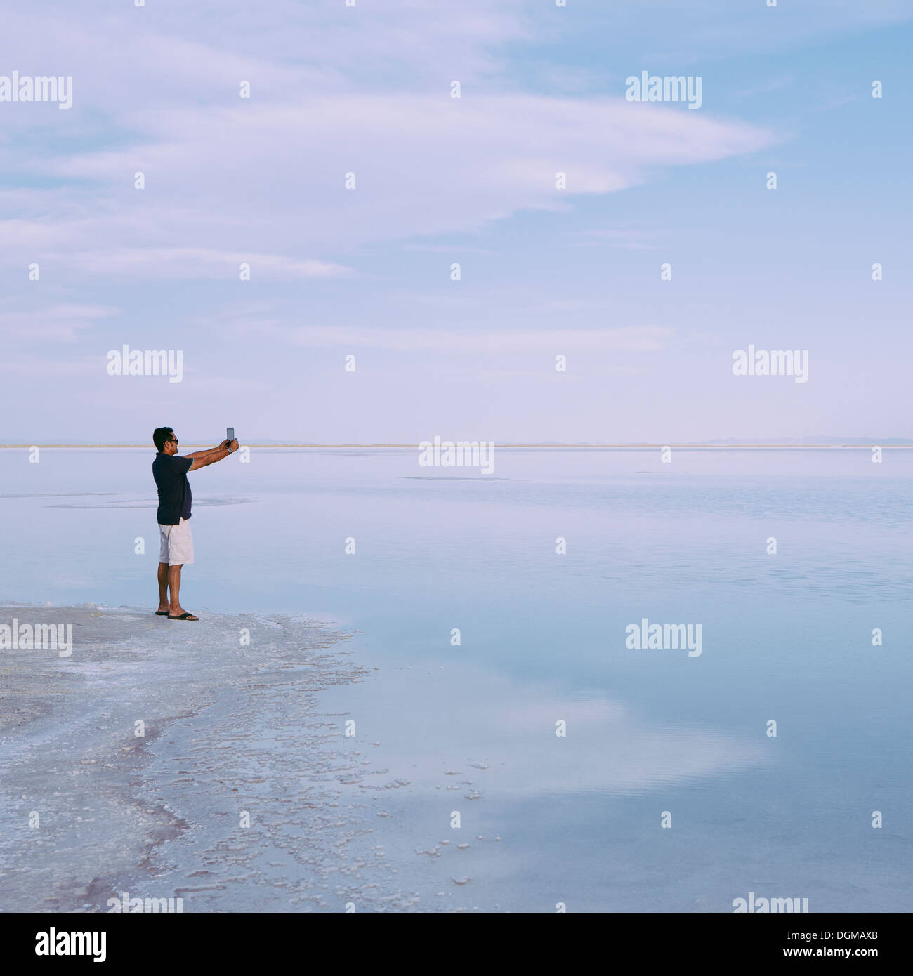 A man standing at edge of the flooded Bonneville Salt Flats at dusk, taking a photograph with a tablet device, near Wendover. - Stock Image