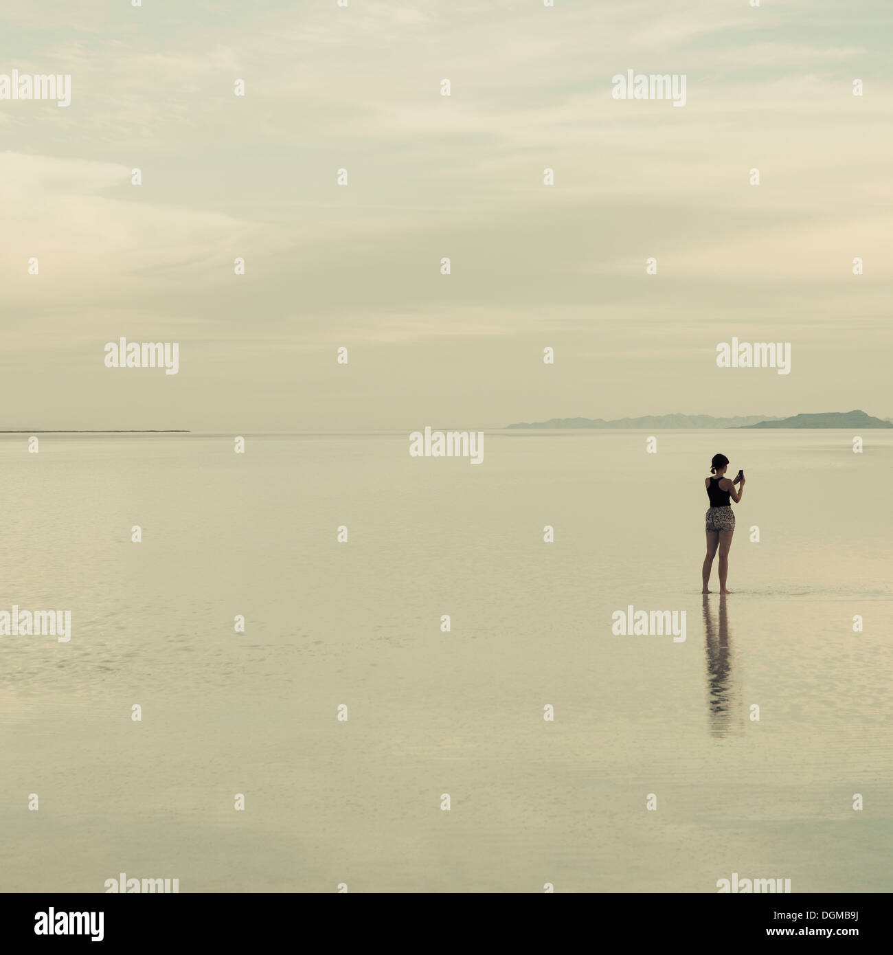 A woman standing on the flooded Bonneville Salt Flats, taking a photograph with a smart phone. - Stock Image