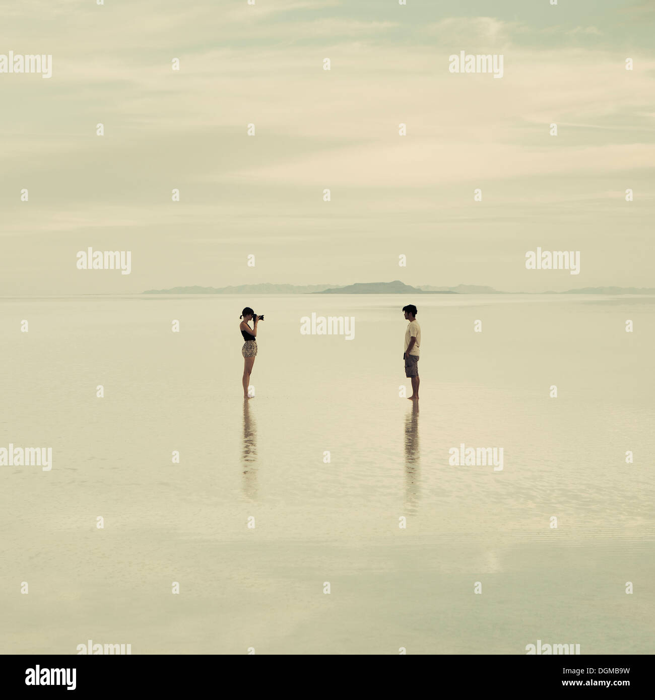 Man and woman standing on the flooded Bonneville Salt Flats, taking photographs of each other at dusk. - Stock Image