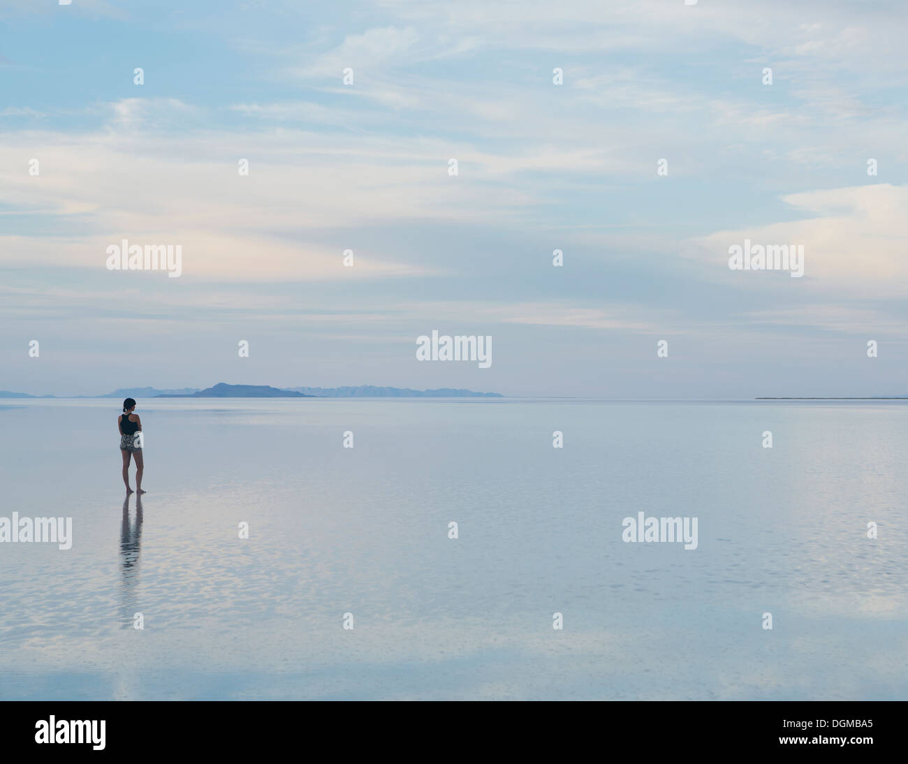 A woman standing on the flooded Bonneville Salt Flats at dusk. Reflections in the shallow water. - Stock Image