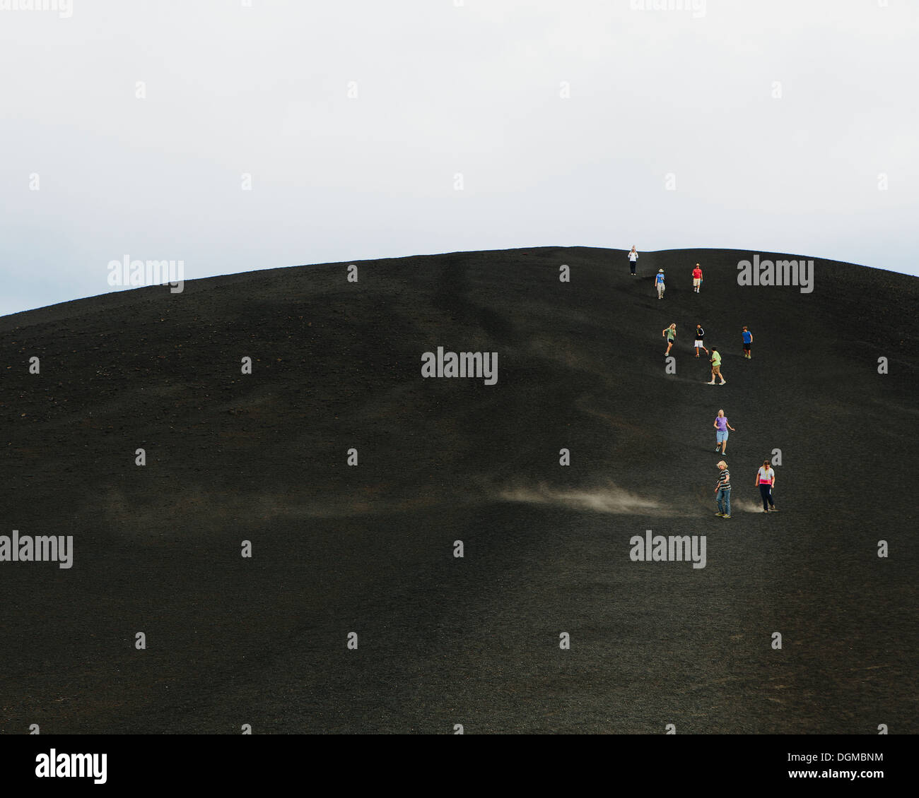 A black volcanic cone hillside in Craters of Moon national monument preserve in Butte County Idaho People walking on slope. - Stock Image