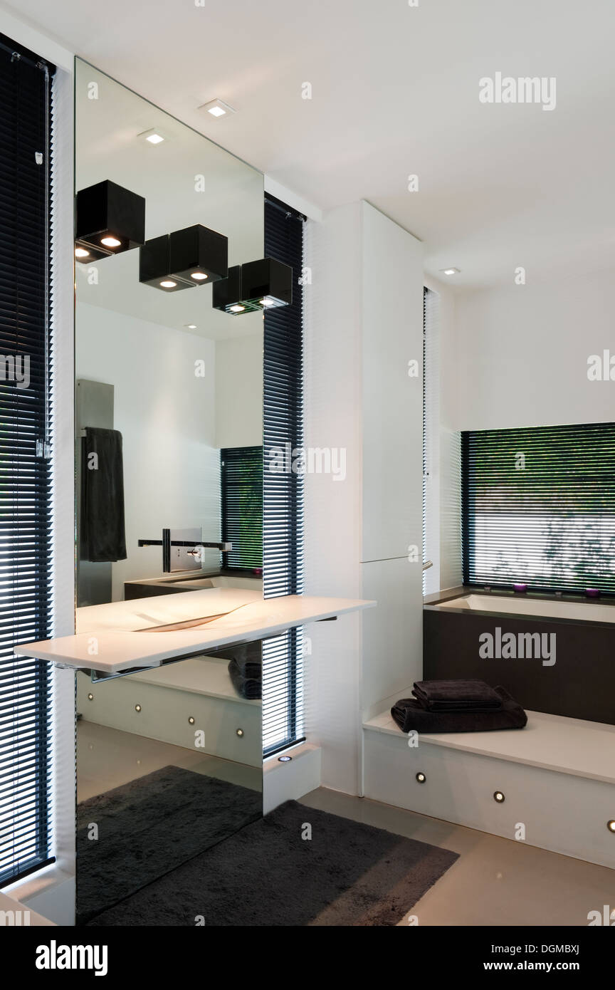 Monochrome bathroom with spotlit mirror - Stock Image