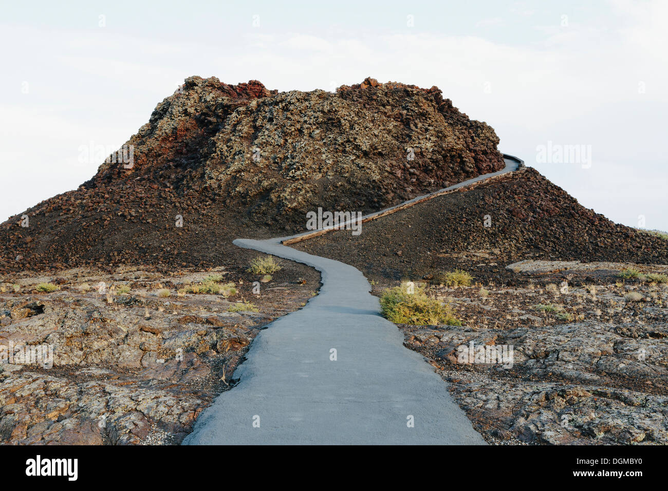 A paved pathway up into the lava fields of the Craters of the Moon national monument and preserve in Butte County Idaho. - Stock Image