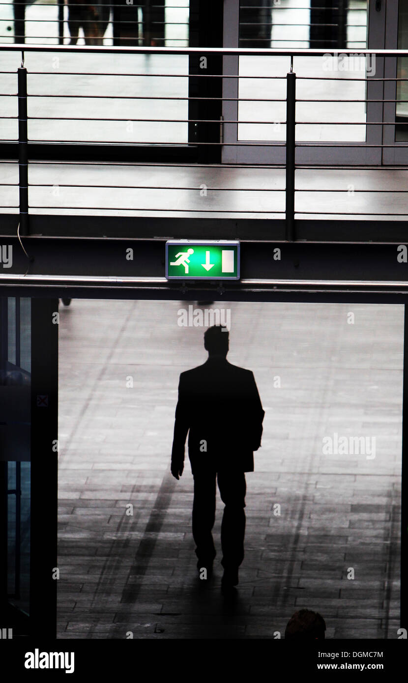 Businessman below an emergency exit sign - Stock Image