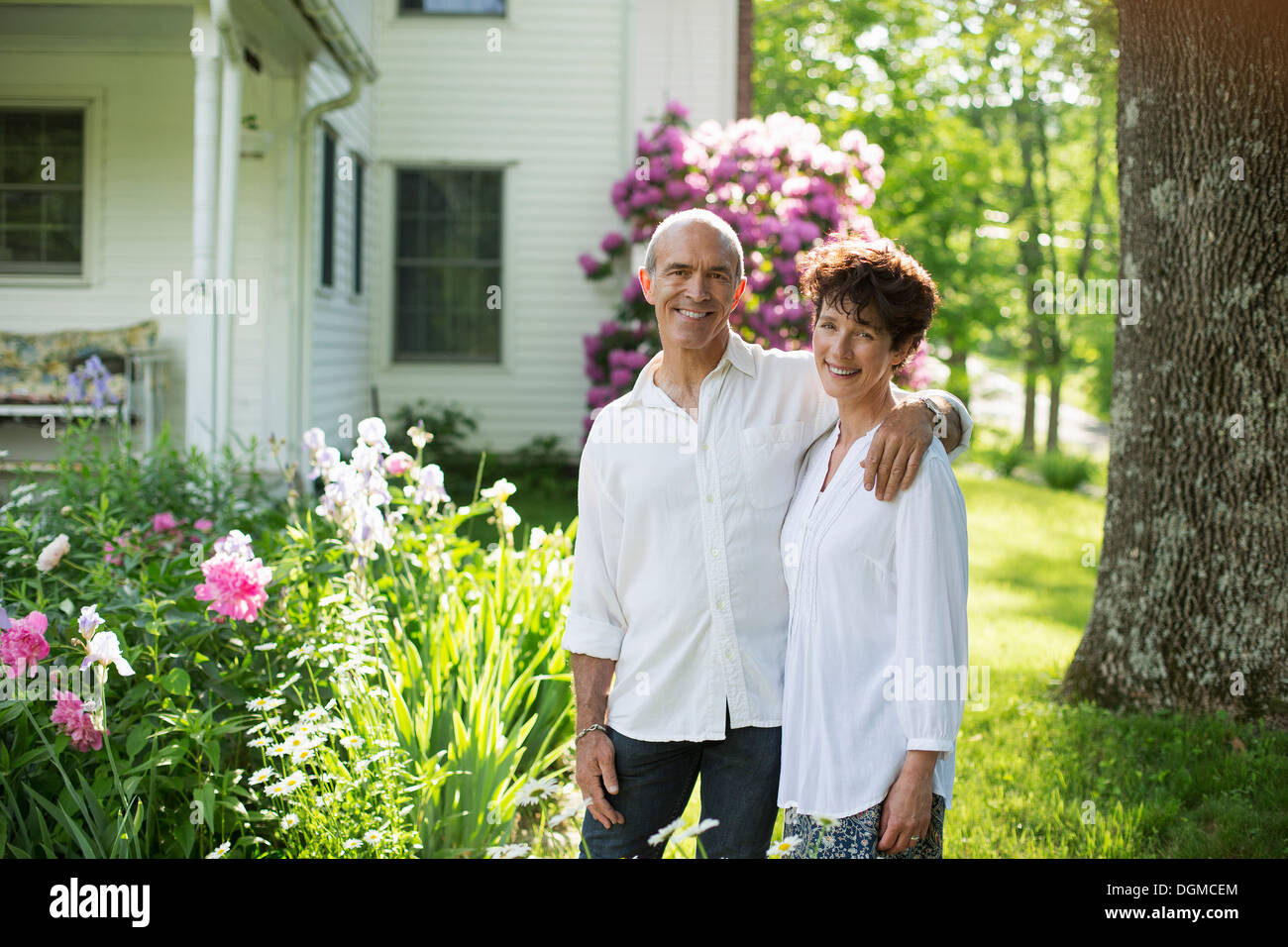 Organic farm. Summer party. A mature couple in white shirts standing together among the flowers. - Stock Image