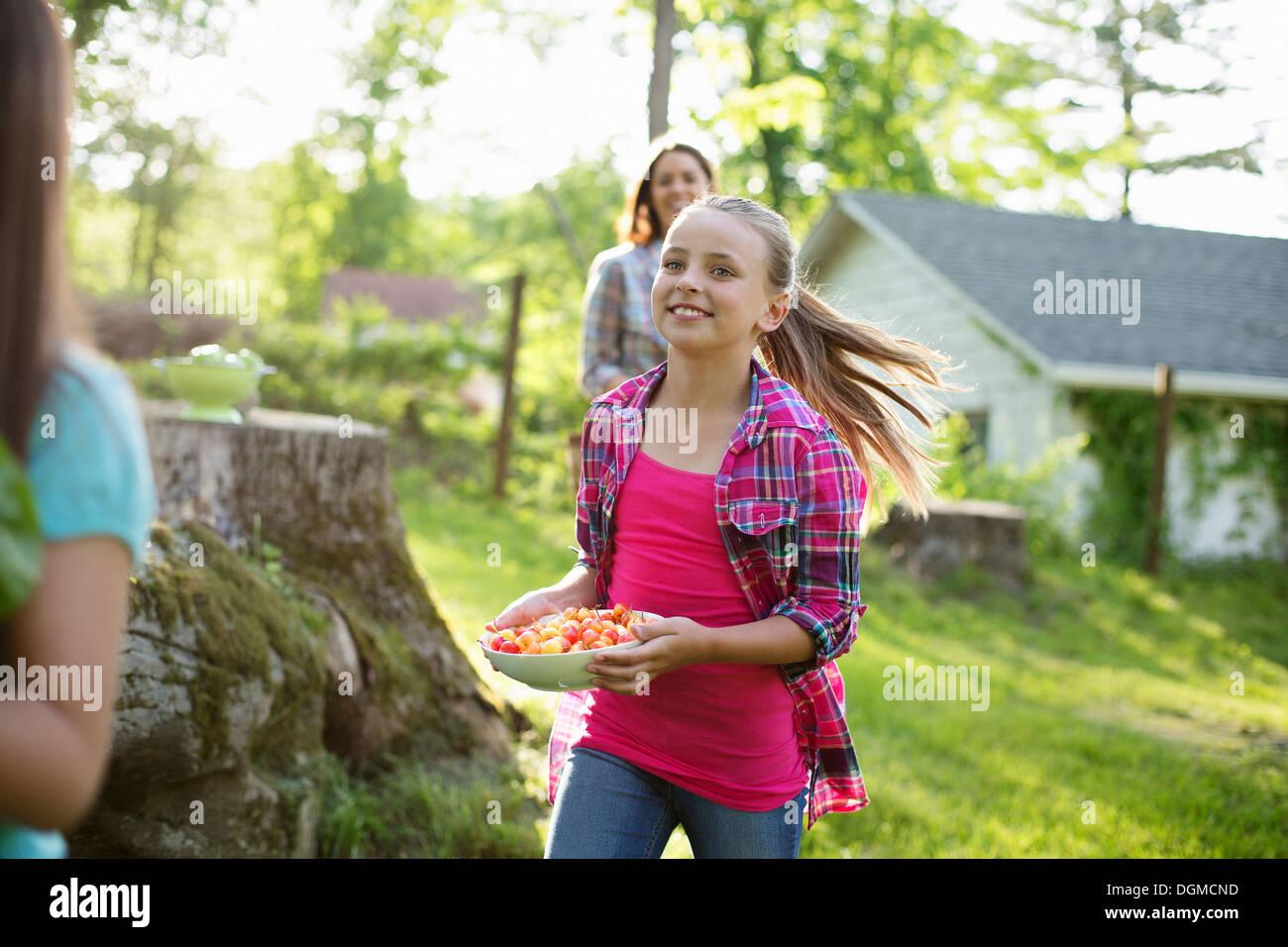 Organic farm. Summer party. Three girls running across the grass. - Stock Image