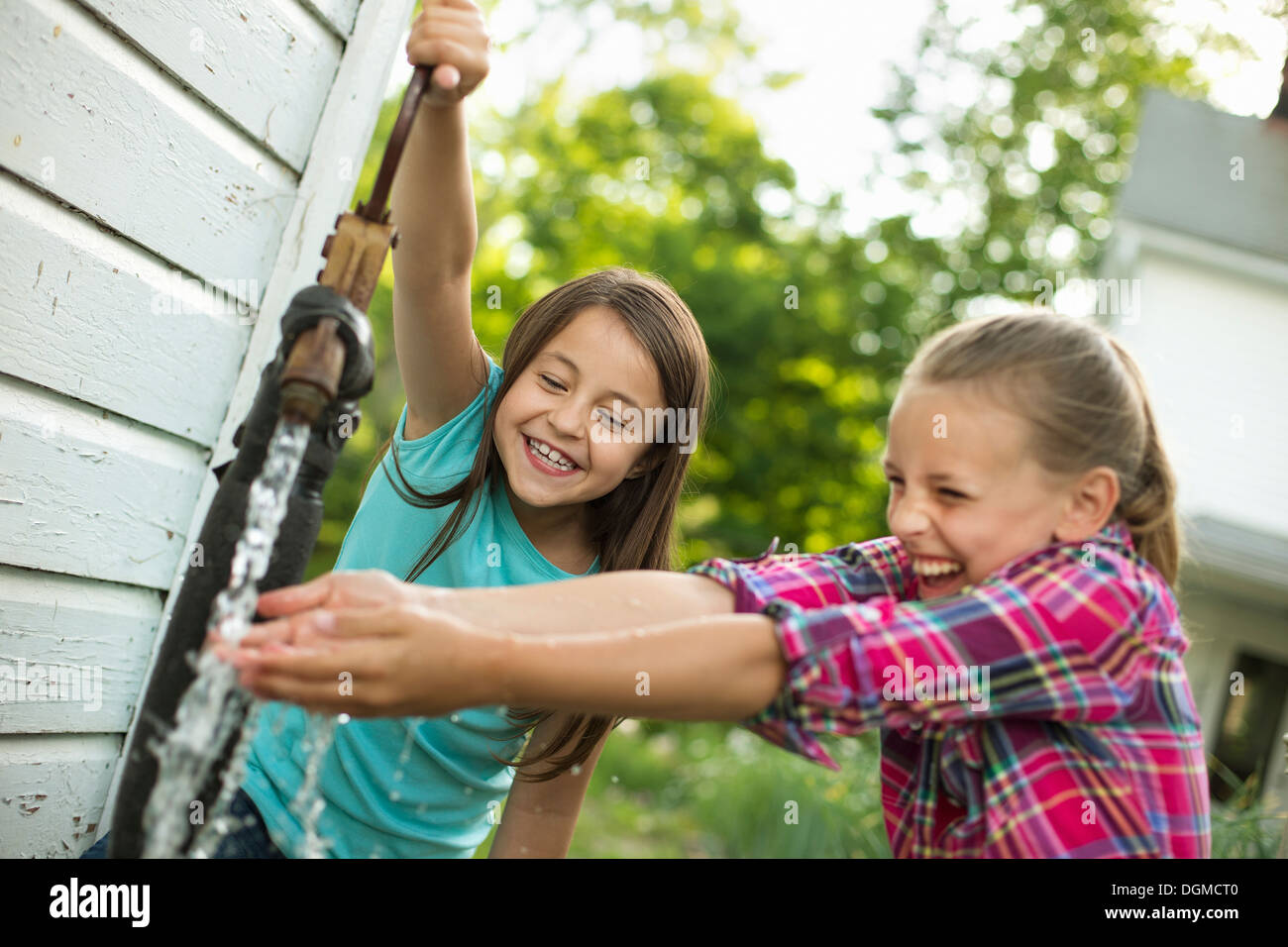 Organic farm. Two girls washing their hands under the flow of water from a pump in the yard. - Stock Image