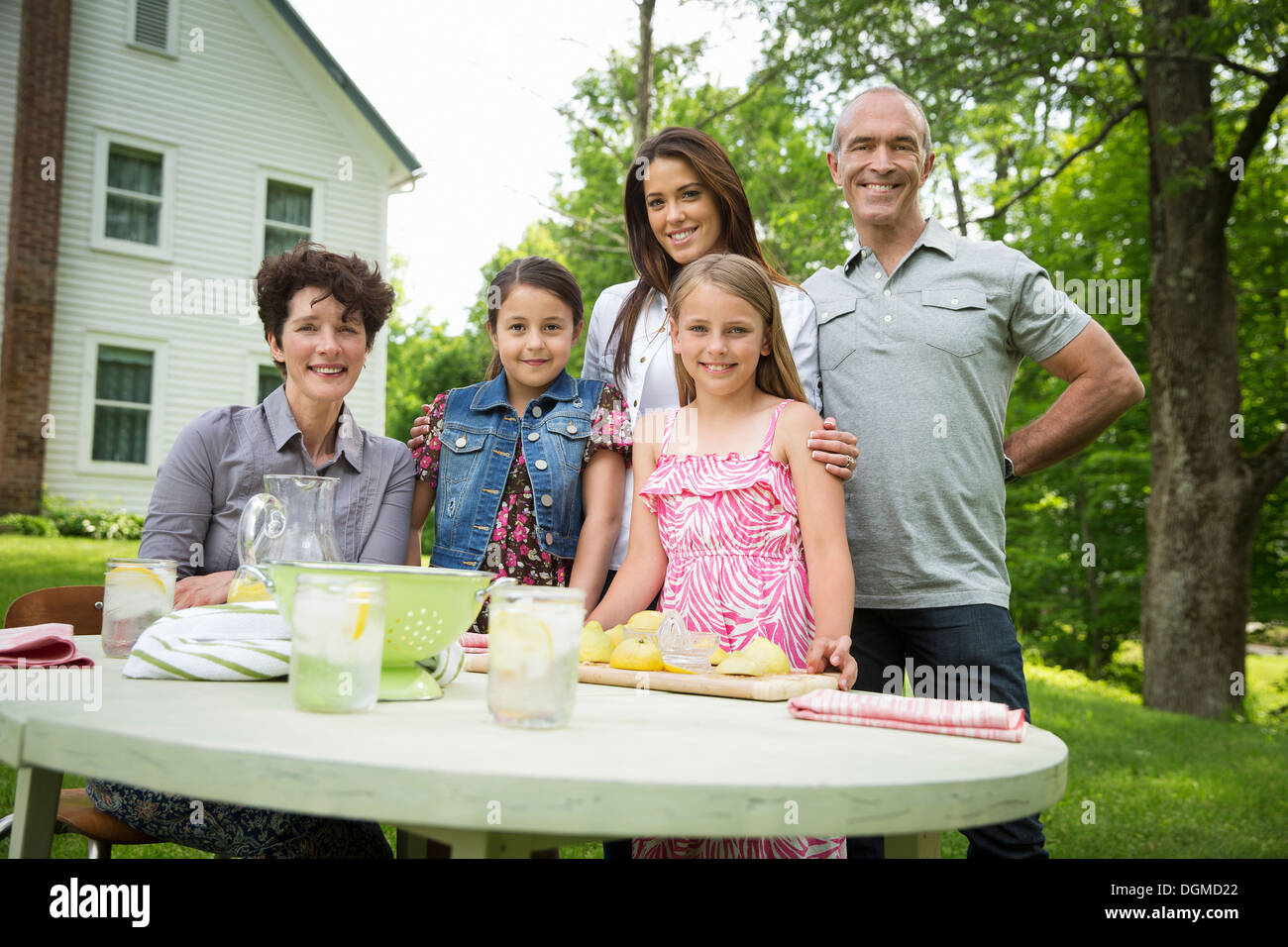 A summer family gathering at a farm. Five people posing beside the table, where a child is making fresh lemonade. - Stock Image