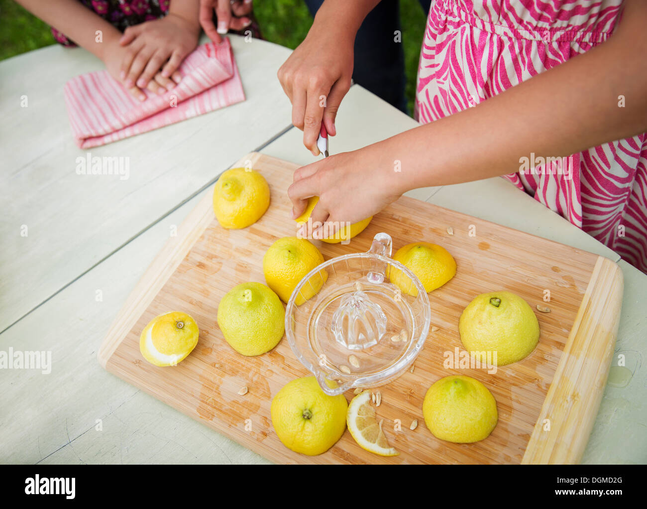 A summer family gathering at a farm. A tabletop chopping board. A child cutting up lemons and juicing them for lemonade. - Stock Image