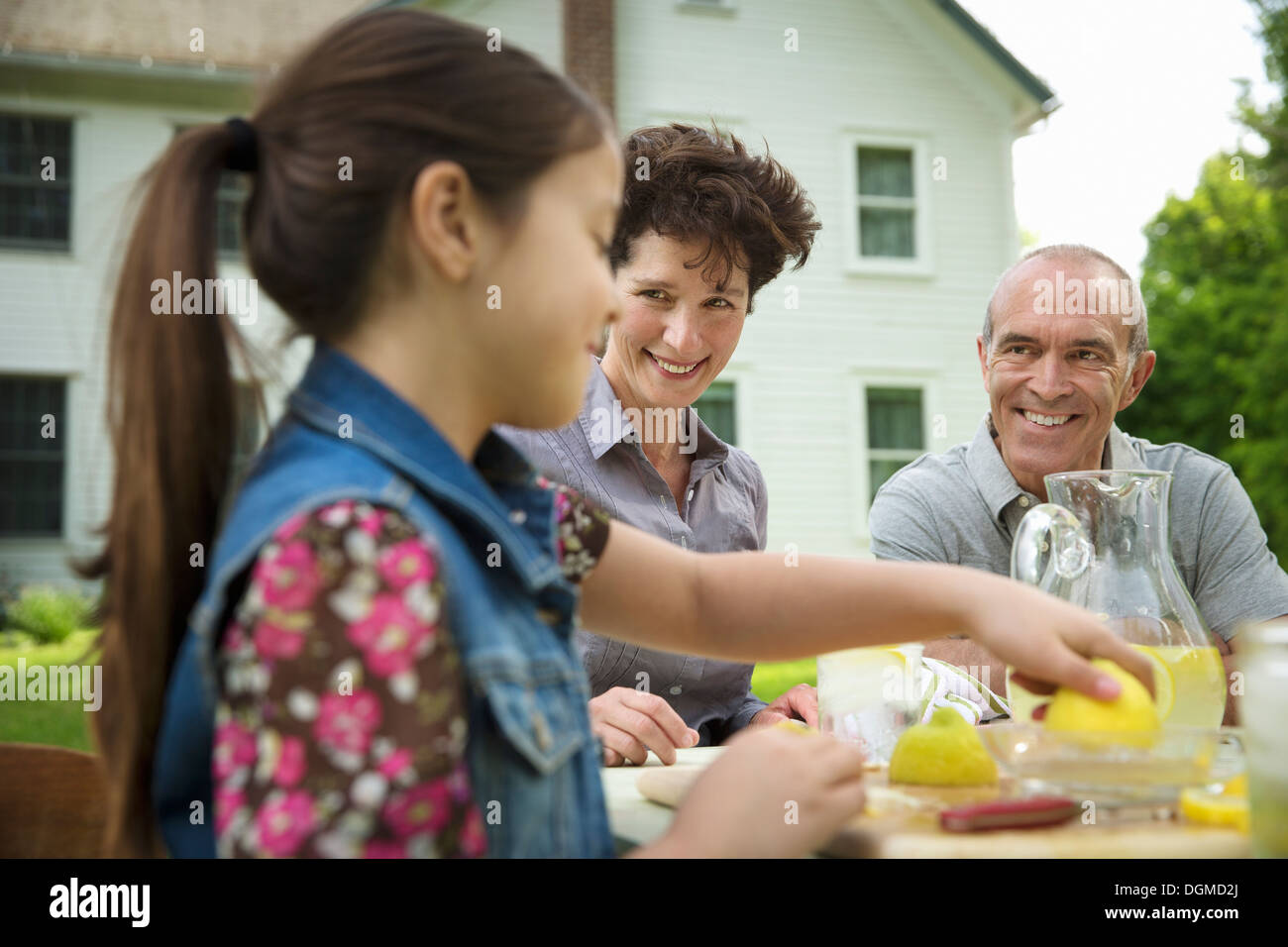 A summer family gathering at a farm. A family group, parents and children. Making fresh lemonade. Stock Photo