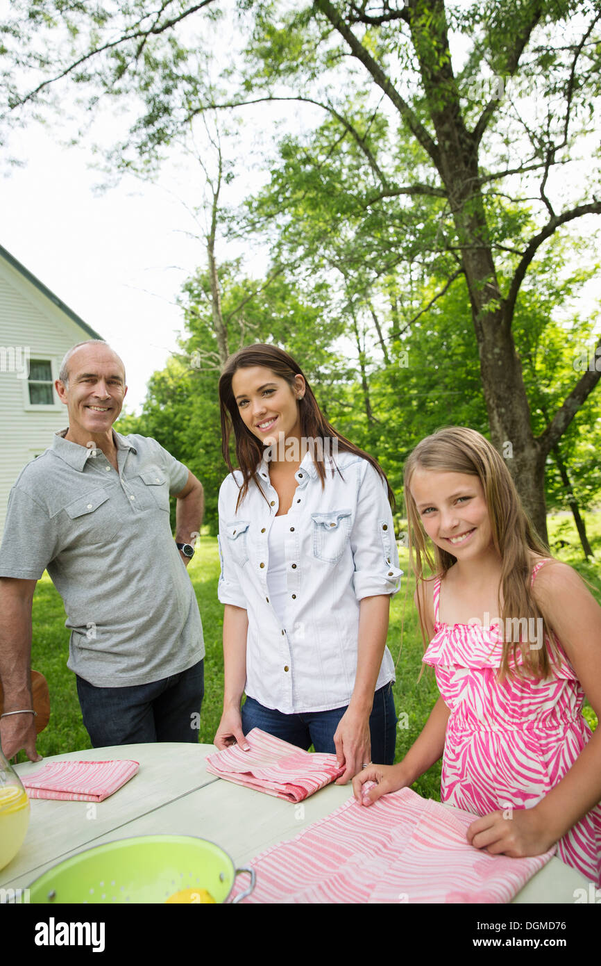 A summer family gathering at a farm. Three people standing by a table, father and daughters. Two girls and a mature man. - Stock Image