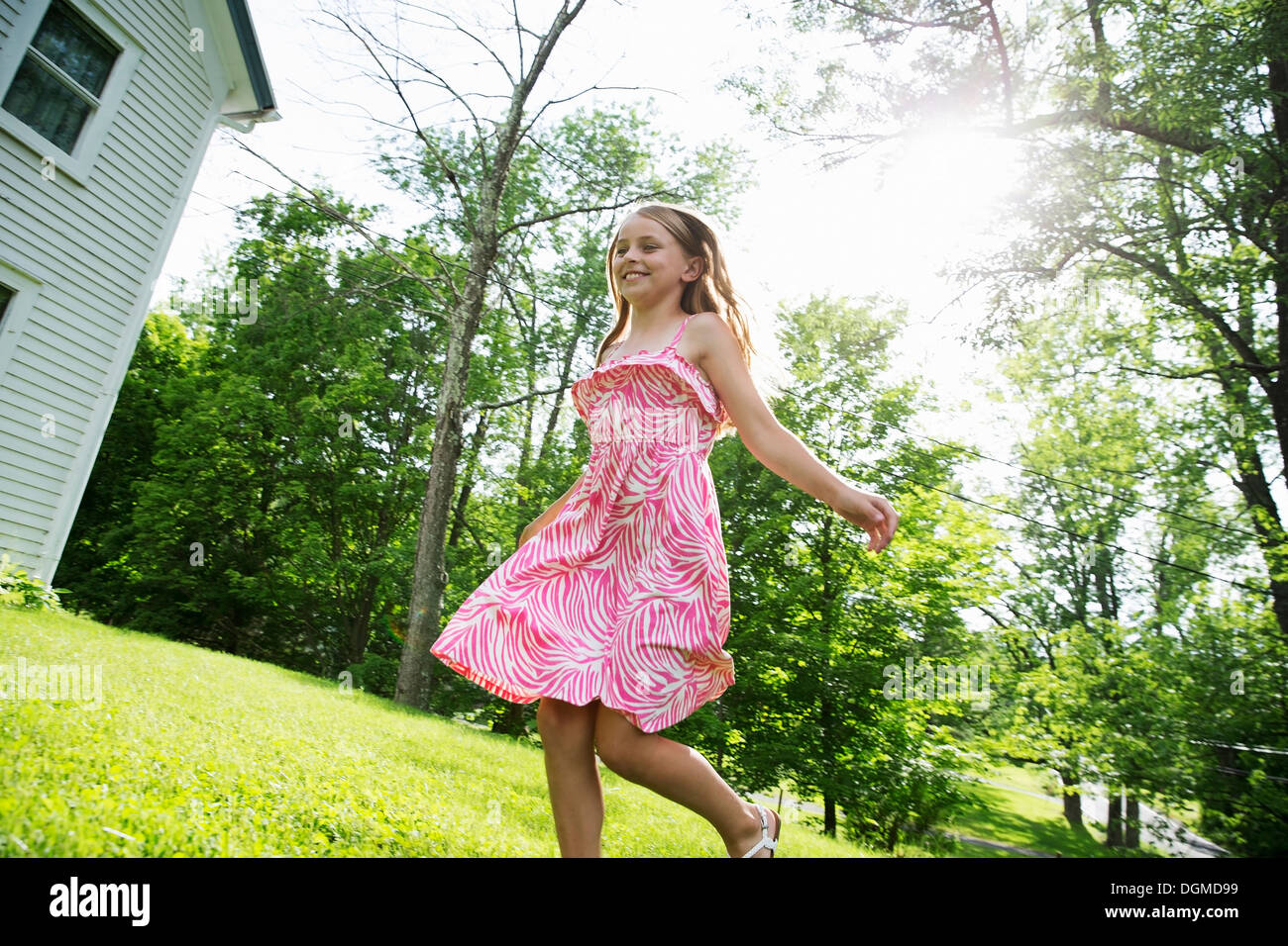 A young girl in a pink patterned sundress running across the grass under the trees in a farmhouse garden. - Stock Image