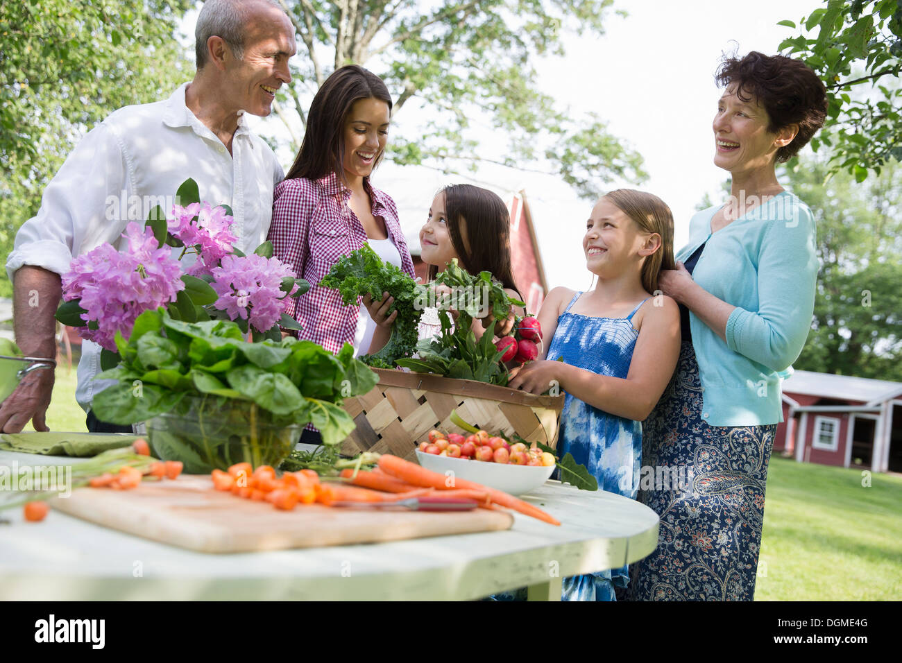 Family party. A table laid with salads and fresh fruits and vegetables. Parents and children. - Stock Image