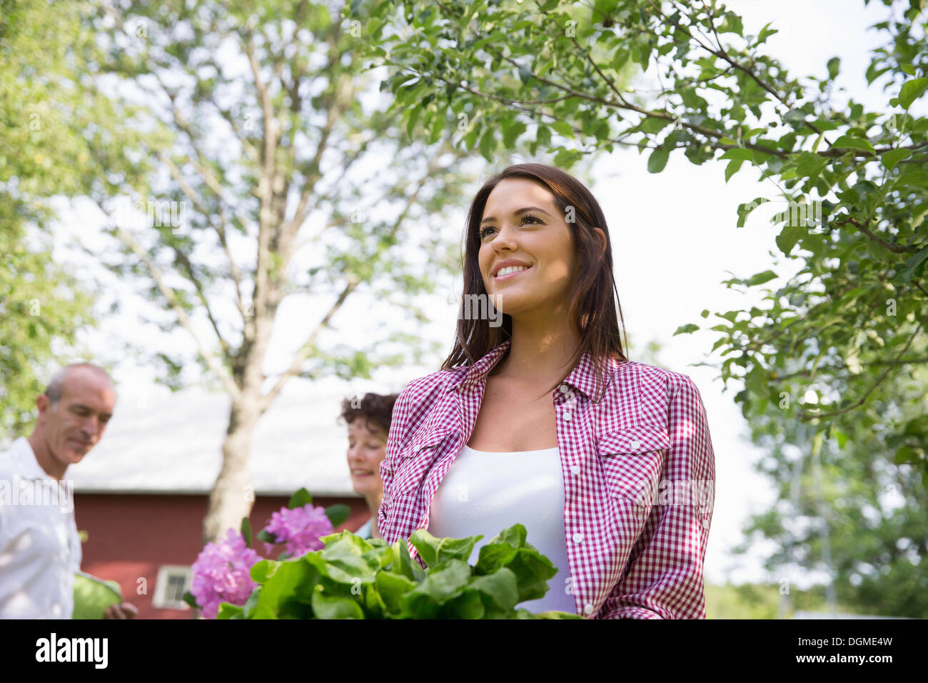 Family party. Three people, a man and woman, and a young girl carrying a bowl full of salad leaves. - Stock Image