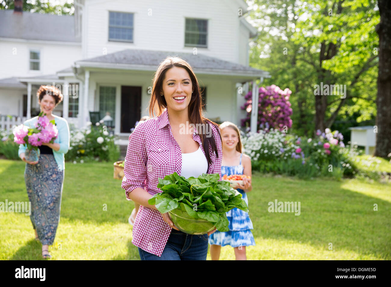 Family party. Parents and children carrying flowers, fresh picked vegetables and fruits. Preparing for a party. Stock Photo