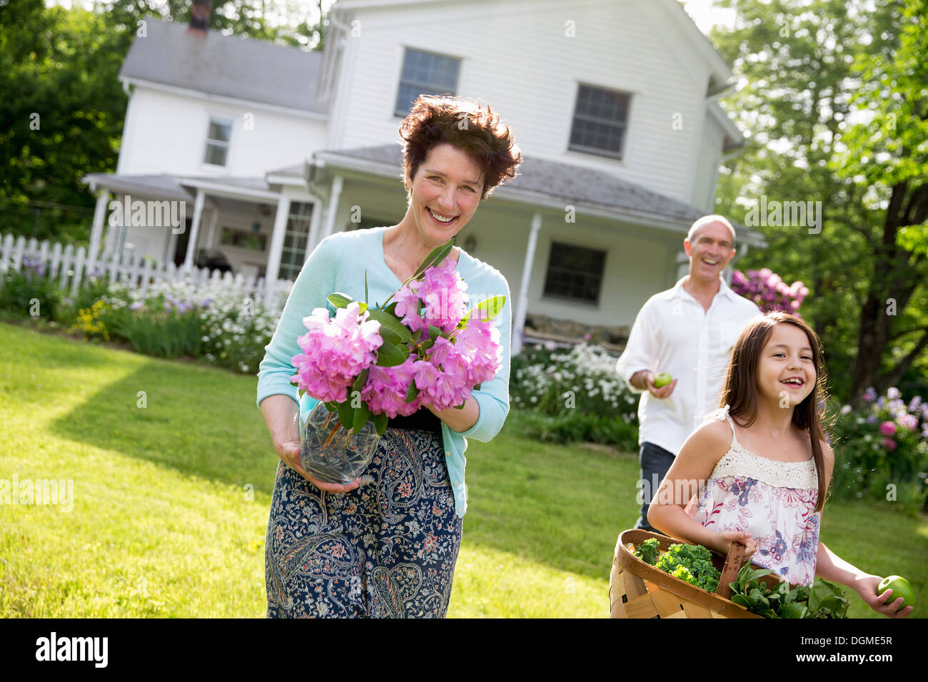 Family party. Parents and children walking carrying flowers, fresh picked vegetables and fruits. Preparing for a - Stock Image