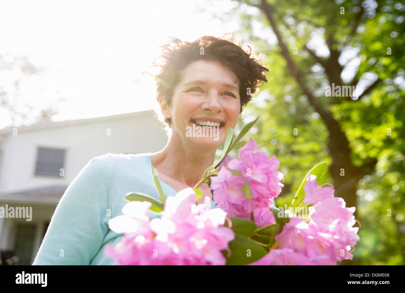 Family party. A woman carrying a large bunch of rhododendron flowers, smiling broadly. - Stock Image