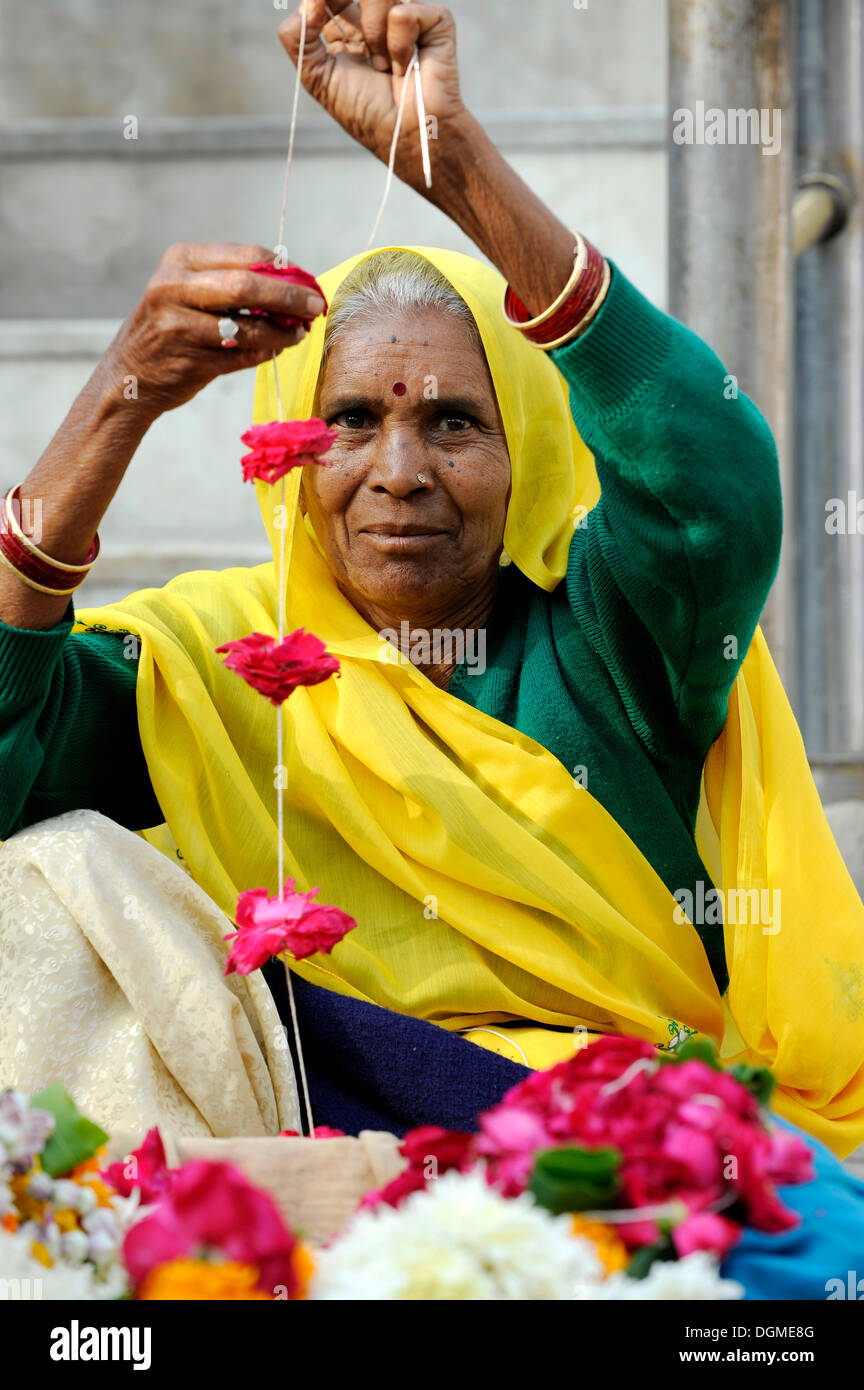 Indian Women manufactures and sells flower garlands in front of the Jagdish temple in Udaipur, Rajasthan, North India, India - Stock Image