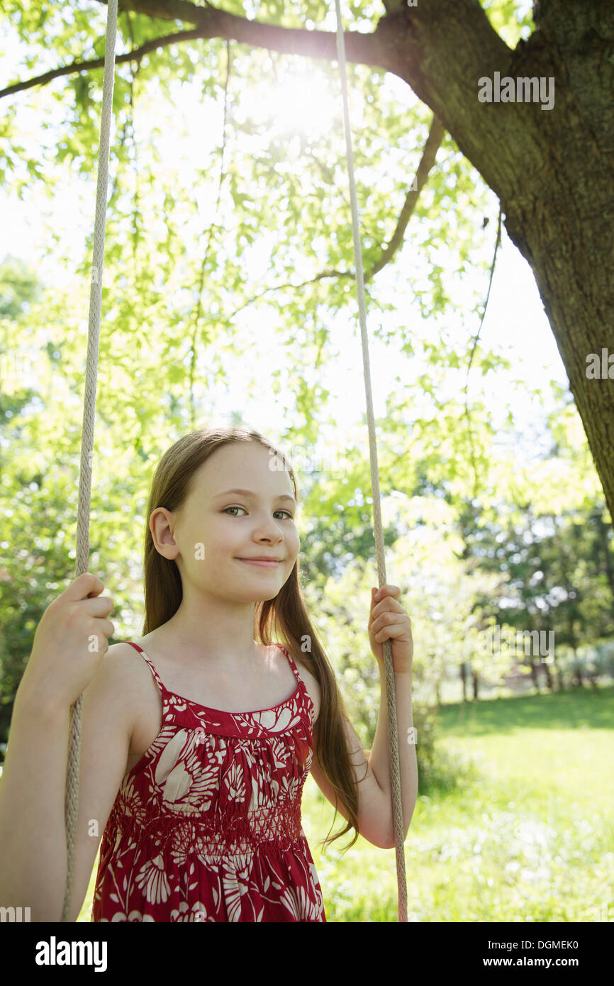 Summer. A girl in a sundress on a swing in an orchard. - Stock Image