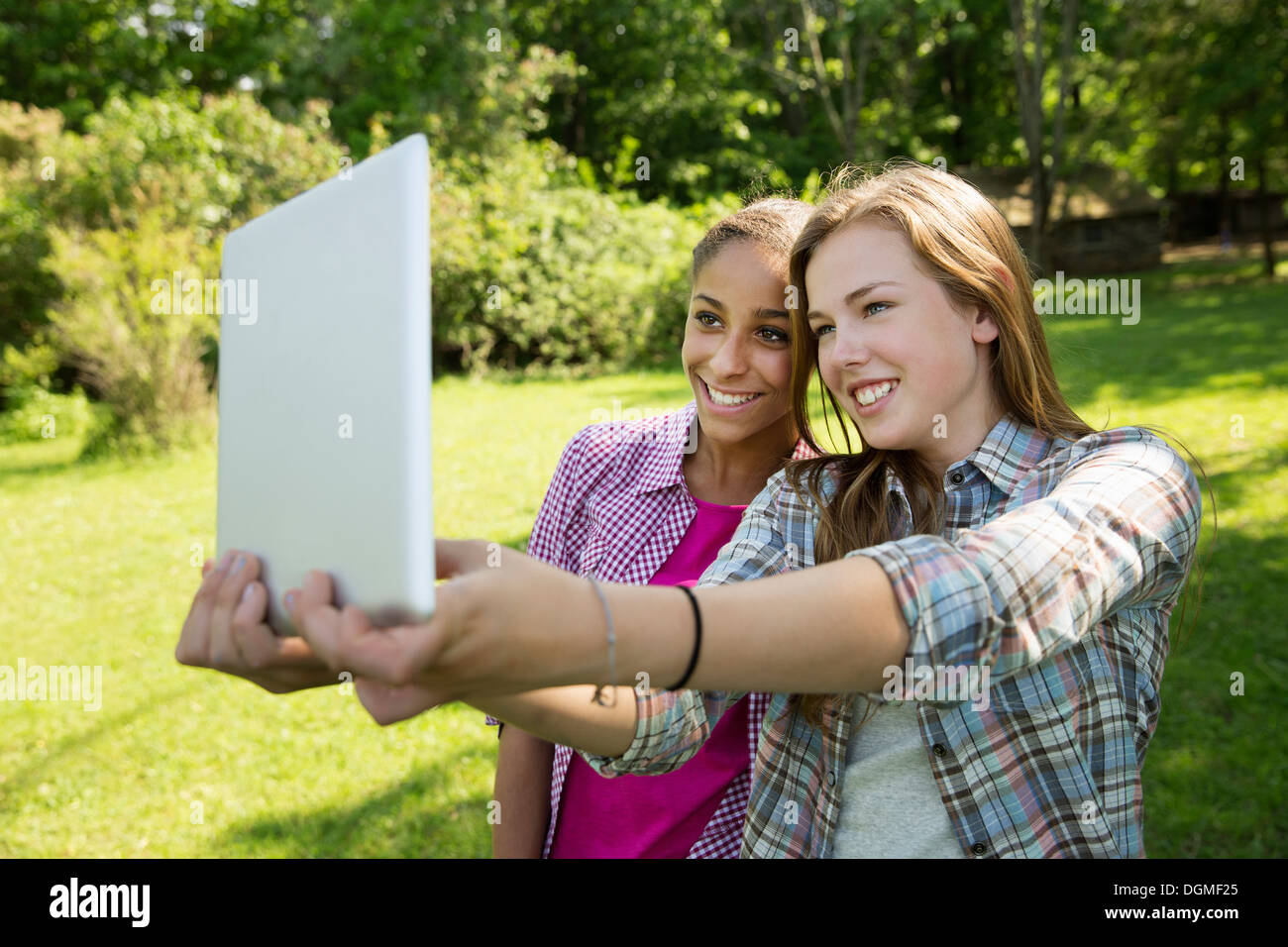 Two girls sitting outdoors on a bench, using a digital tablet. Holding it out at arm's length. - Stock Image