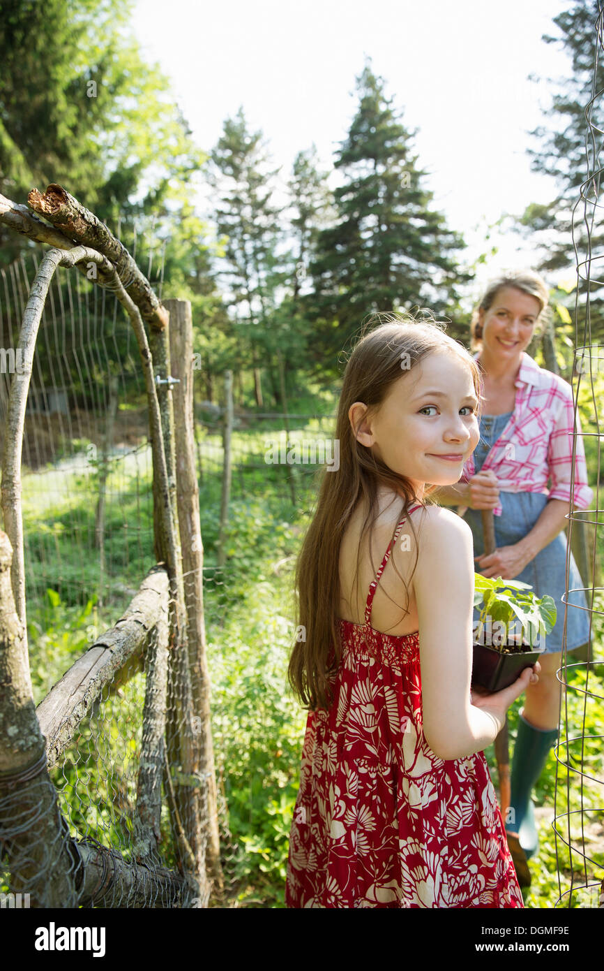 A woman and a child standing at the open gate of a fenced enclosure. A girl holding a small plant in a pot. - Stock Image