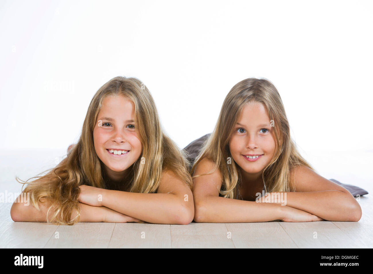 Twin girls, 9, lying on their bellies and smiling - Stock Image