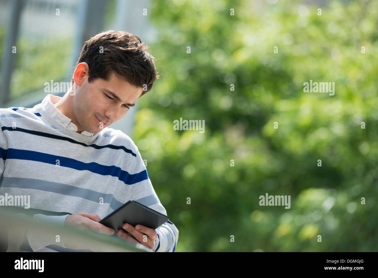 Summer. Business people. A man sitting using a digital tablet, keeping in touch. - Stock Image