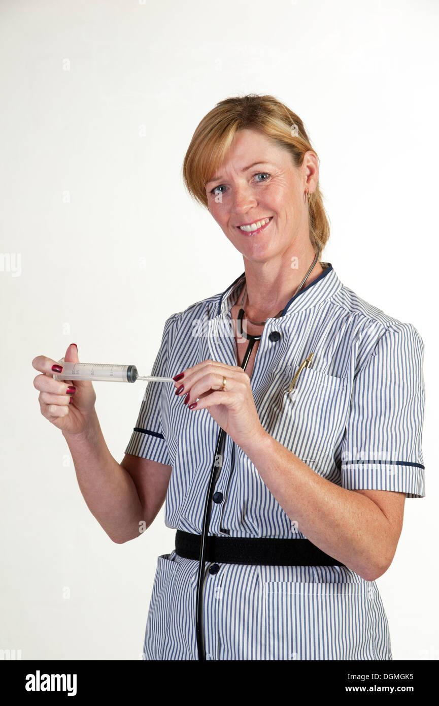 Nurse holding a large syringe - Stock Image